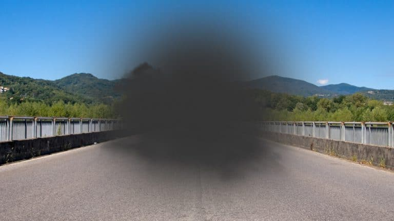 Picture of the view out a car window with a large grey blind spot in the center