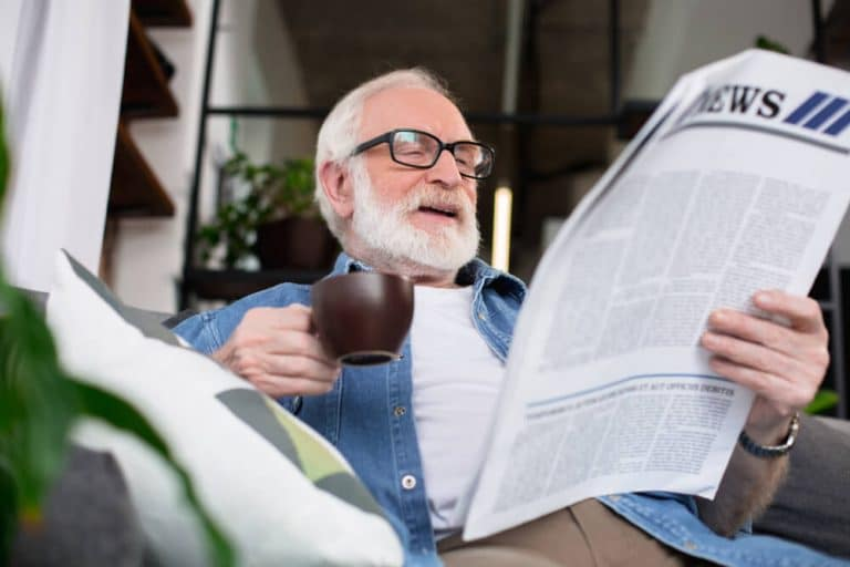 Picture of an older man holding a coffee cup and smiling reading a newspaper